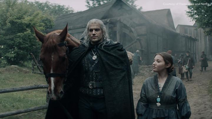 Henry Cavill as Geralt of Rivia walking with child